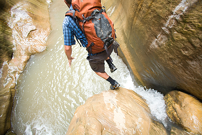 Dave Littman jumps into a pools of water in Orderville Canyon, Zion National Park
